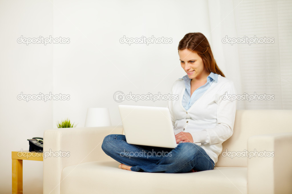 Portrait of a young lovely woman working on sofa with a laptop  Stock Photo #10218922
