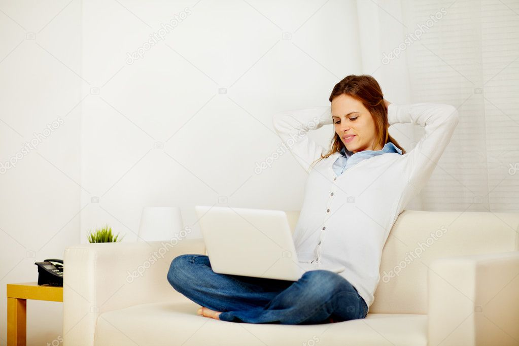 Portrait of a young lovely woman resting on sofa with a laptop  Stock Photo #10218928