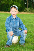 Boy sits on soccer ball — Stock Photo