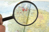 Magnifying Glass in front of a map — Stock Photo