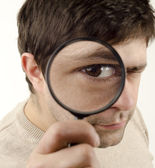 Young man looking throught magnifying glass — Stock Photo