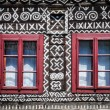Red windows on wooden wall of traditional cottage — Stock Photo #10408813