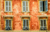 Vintage red wall with wooden windows — Stock Photo