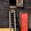 Wooden ladder on a cottage wall with red door - Stock Photo