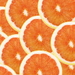 Fresh grapefruit and slices background - Stockfoto