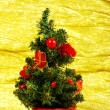 Royalty-Free Stock Photo: Little decorated christmas tree on golden background with gifts