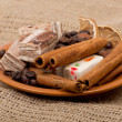 Sweets, cinnamon, nuts and coffee beans on a saucer, on burlap b - Stock Photo