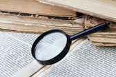 Magnifier and old books — Stock Photo