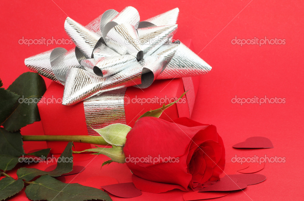 Valentines Day gift in box with rose and small hearts on red background — Stock Photo #8526546