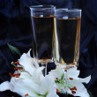 Glasses with wine and lily flower on black silk — Stock Photo #9419806