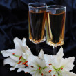 Glasses with wine and lily flower on black silk — Stock Photo