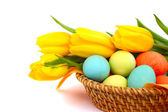 Easter eggs in basket with tulips — Stock Photo