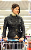 Ung kvinna med kundvagn — Stockfoto