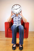 Woman holding a clock covering her face — Stock Photo