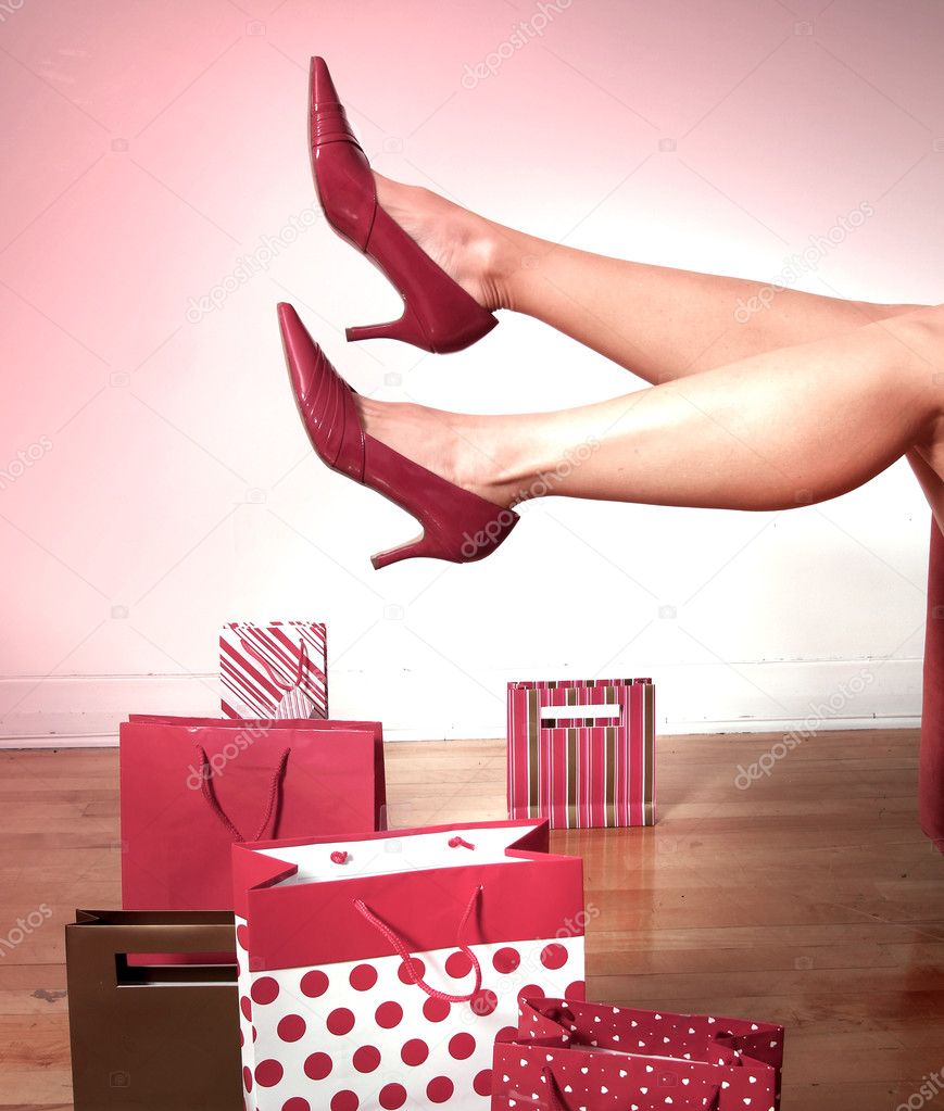 Two woman legs with red shoes in the air with red shopping bags on a floor — Stock Photo #9258215