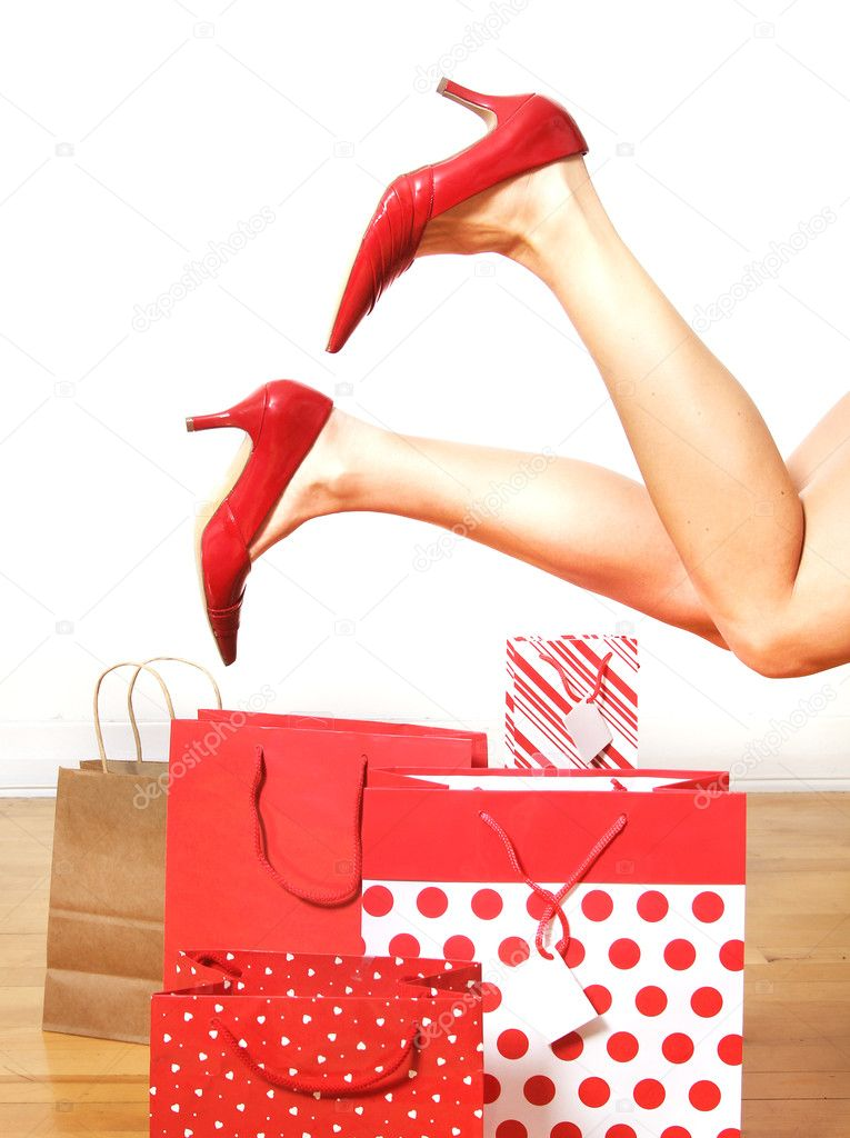 Two woman legs with red shoes in the air with red shopping bags on a floor  Stock Photo #9391282