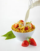 Pouring milk in a red cornflakes bowl with strawberries over white background — Stock Photo