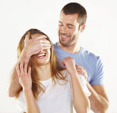 Happy man covering young beautiful girl eyes wanting to surprise her — Stock Photo