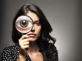 Beautiful woman looking through a magnifying glass — Stock Photo