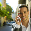 Stock Photo: Happy business man making calls with smartphone in city