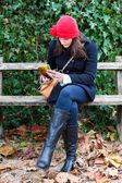 Mujer sentada en un banco y leyendo un libro — Foto de Stock