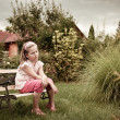 Girl sitting on bench in backyard — Stock Photo #9966409