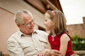 Grandfather with her grandchild ouside in backyard — Stock Photo