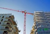 Crane surrounded two buildings under construction, — Stock Photo
