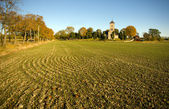 Plowed field and church — Stock Photo