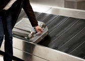 Suitcase on conveyor belt — Stock Photo