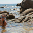 The girl on seacoast flounders about in water. In a mask and flippers — Stock Photo #9886714