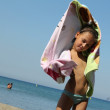 Beach little girl playing with towel and wind in blue sea — Foto Stock