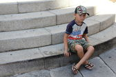 A small boy sitting on stairs — Stock Photo