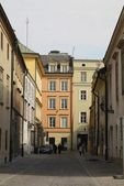 Narrow street and old buildings in centre of Krakow — Stock Photo