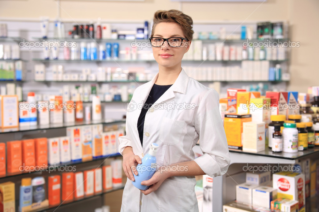 Young female pharmacist holding a bottle of cream — Stock Photo #9643129