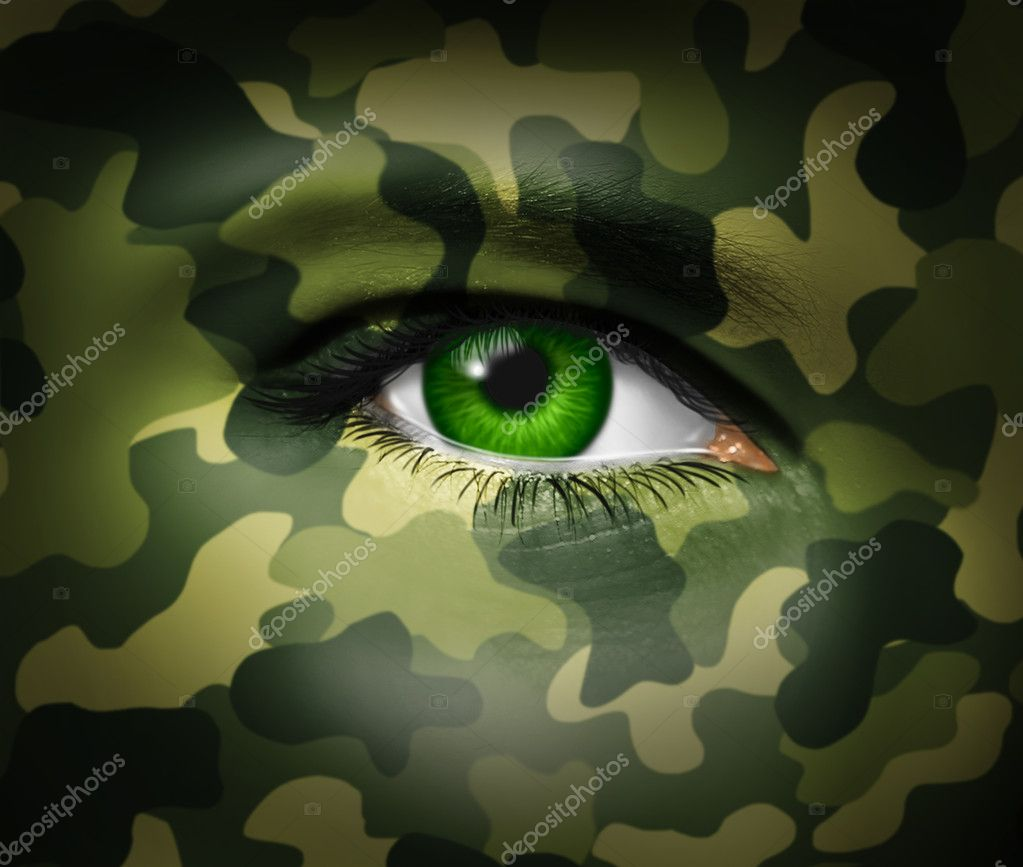 Military camouflage on a human face with a close up of the green eye gazing and looking representing war tactics and battle strategy in an army or business situation.  Stock Photo #10679708