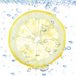 Lemon in a liquid with bubbles. On a white background. — Stock Photo
