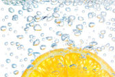 Orange in a liquid with bubbles. On a white background. — Stock Photo