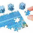 The missing puzzle in the fingers on a white background. — Stock Photo