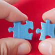 Royalty-Free Stock Photo: Connecting two puzzles. On a red background.