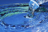 The stream of water flowing from the bottle. — Stock Photo