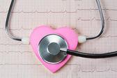 Stetoskop och hjärtat på en bakgrund av elektrokardiogram. — Stockfoto