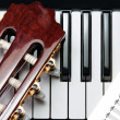 Stock Photo: Element of guitar on piano