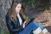 A girl enjoys the tablet, in nature. — Stock Photo