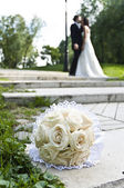 Wedding bouquet with the wedding couple in the background — Stock Photo