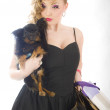 Royalty-Free Stock Photo: Young glamorous blonde with shopping bag holding toy terrier dogs holding dog