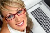 Mujer joven atractiva con gafas delante de un ordenador portátil — Foto de Stock