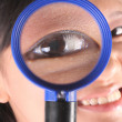 Woman looks through magnifying glass — Stock Photo