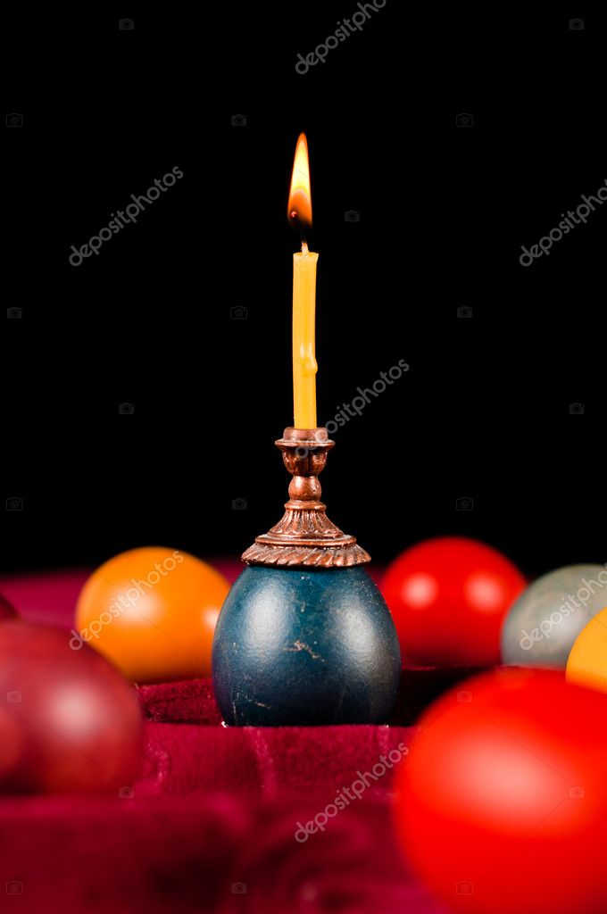 Candle standing on easter egg placed with many others on fabric — Photo #10065973