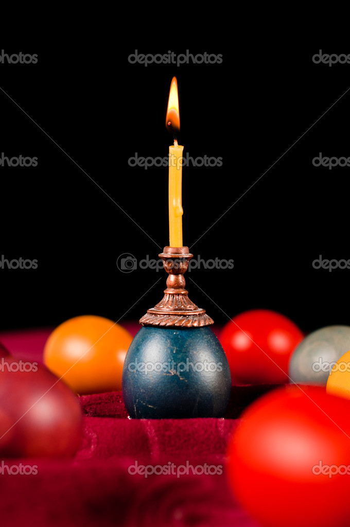 Candle standing on easter egg placed with many others on fabric — Stock Photo #10065973